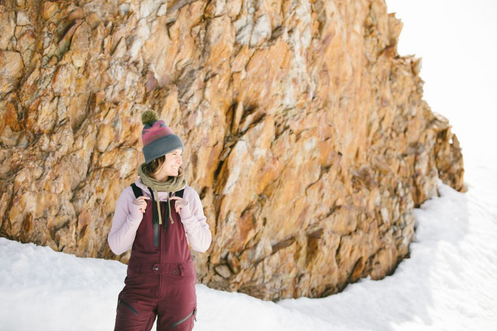 A female skier standing in the snow wearing maroon colored ski bibs