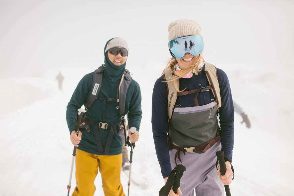 A male and a female skier wearing ski bibs on a white and snowy day