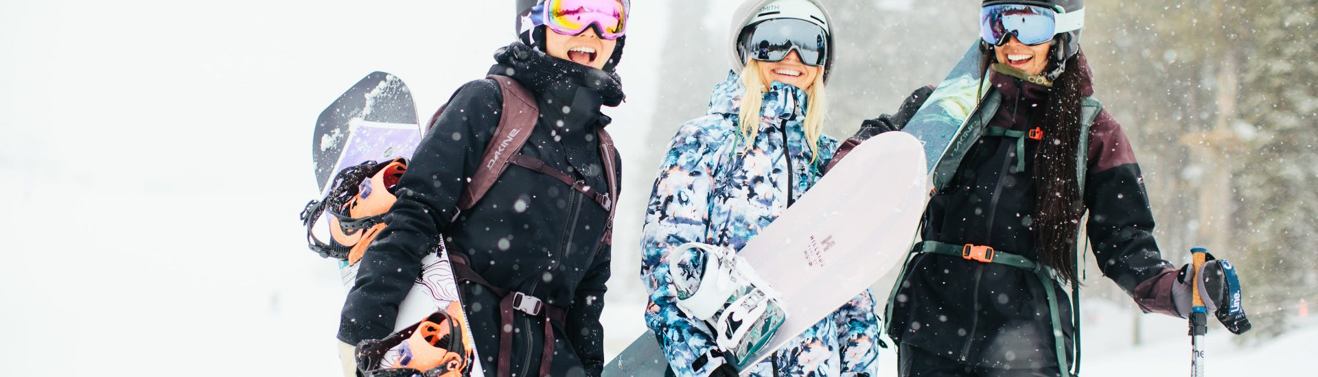 2 female snowboarders and 1 female skier standing together smiling in the snow