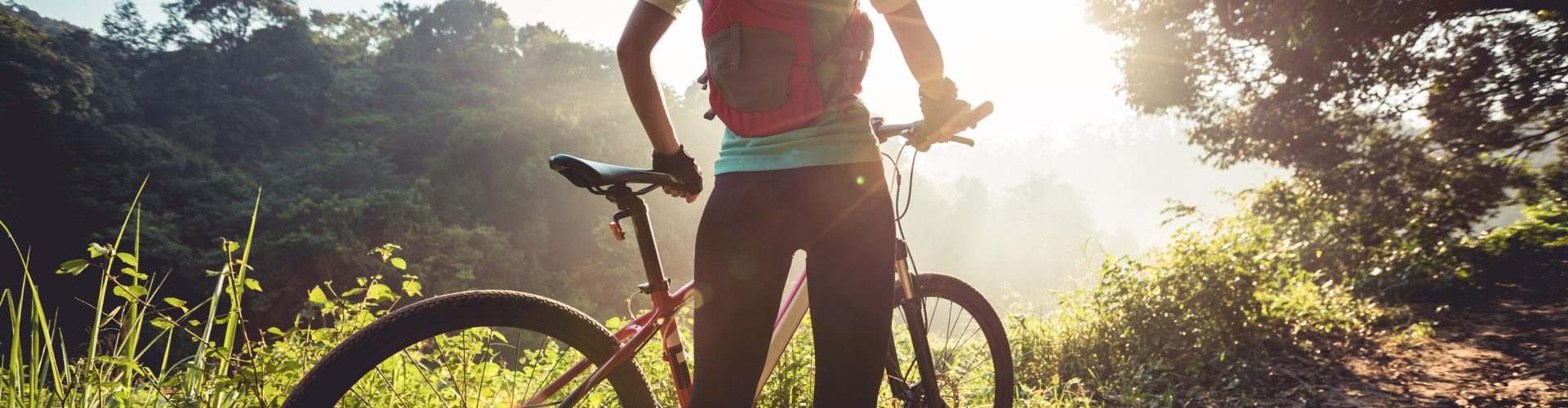 Young woman mountain biker enjoys the beautiful sunrise on summer forest trail