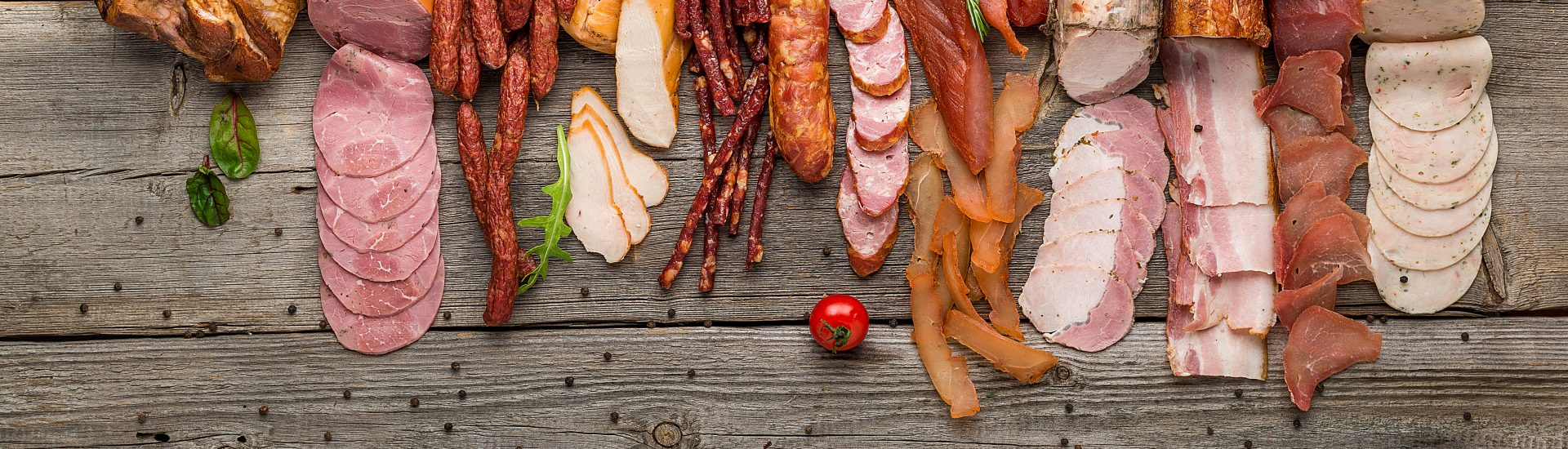 Assortment of cold meats, variety of processed cold meat products. On a wooden background