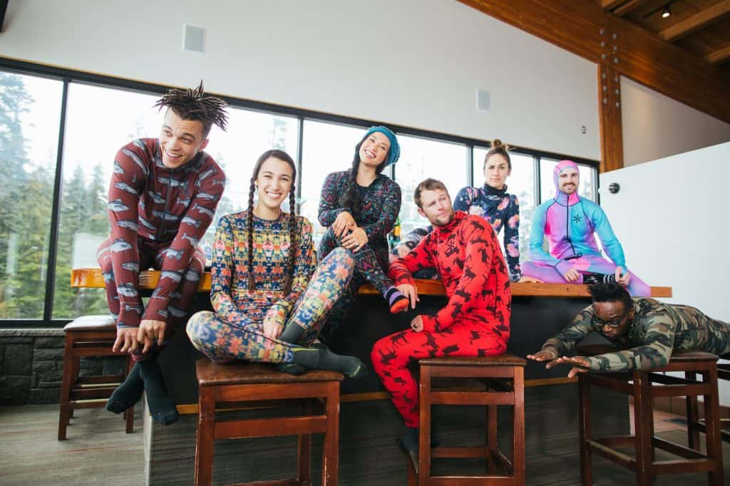 A group of smiling, happy, young skiers dressed in colorful base layers in a ski lodge