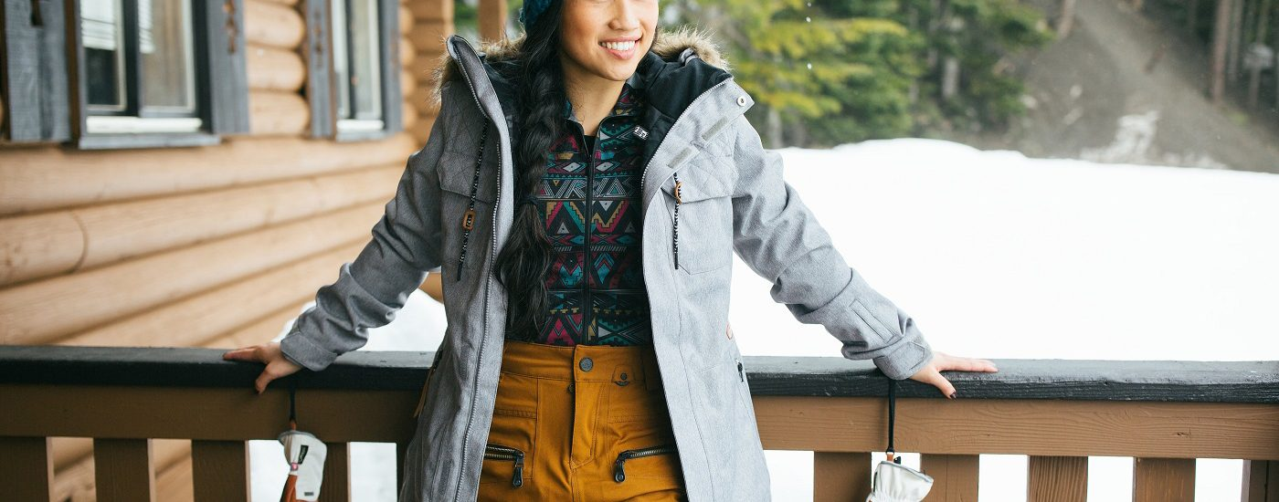 A young female skier wearing colorful gear standing on a covered porch in the snow