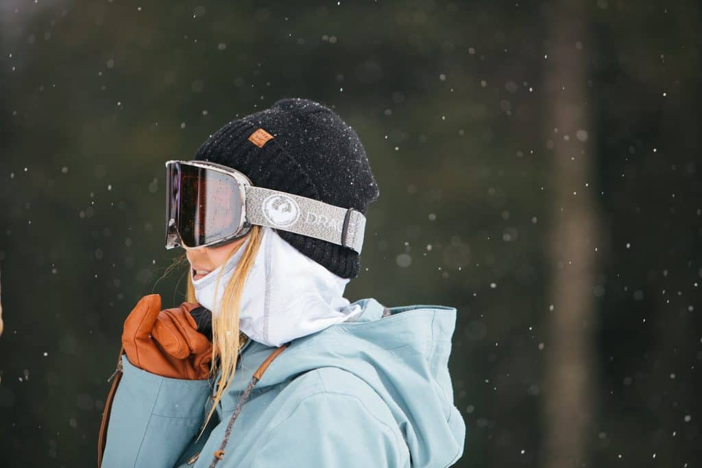 A young female skier with snow falling wearing ski goggles, ski jacket, gloves and a hat
