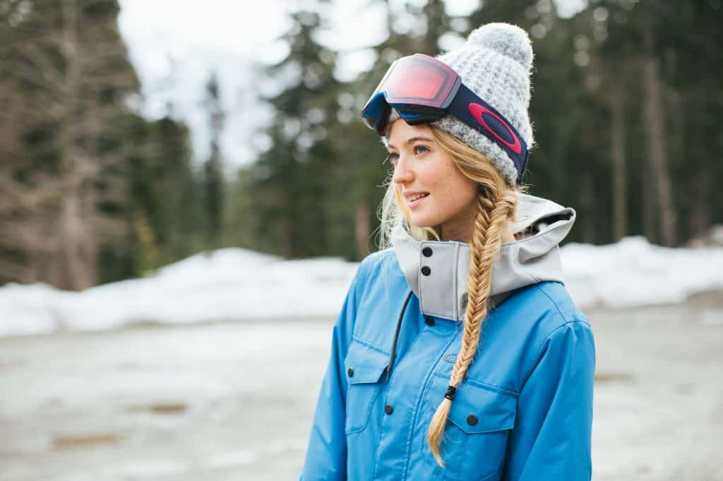A young female skier wearing a blue jacket, a hat and ski goggles