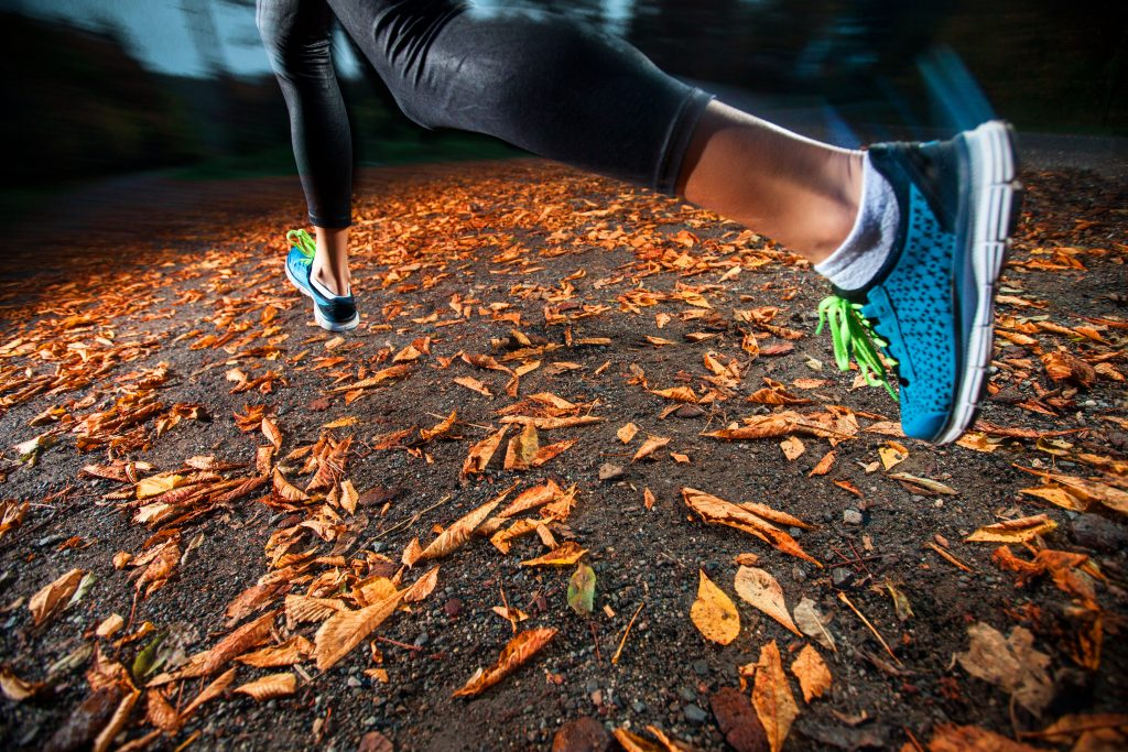 young woman trail running in the early evening autumn leaves