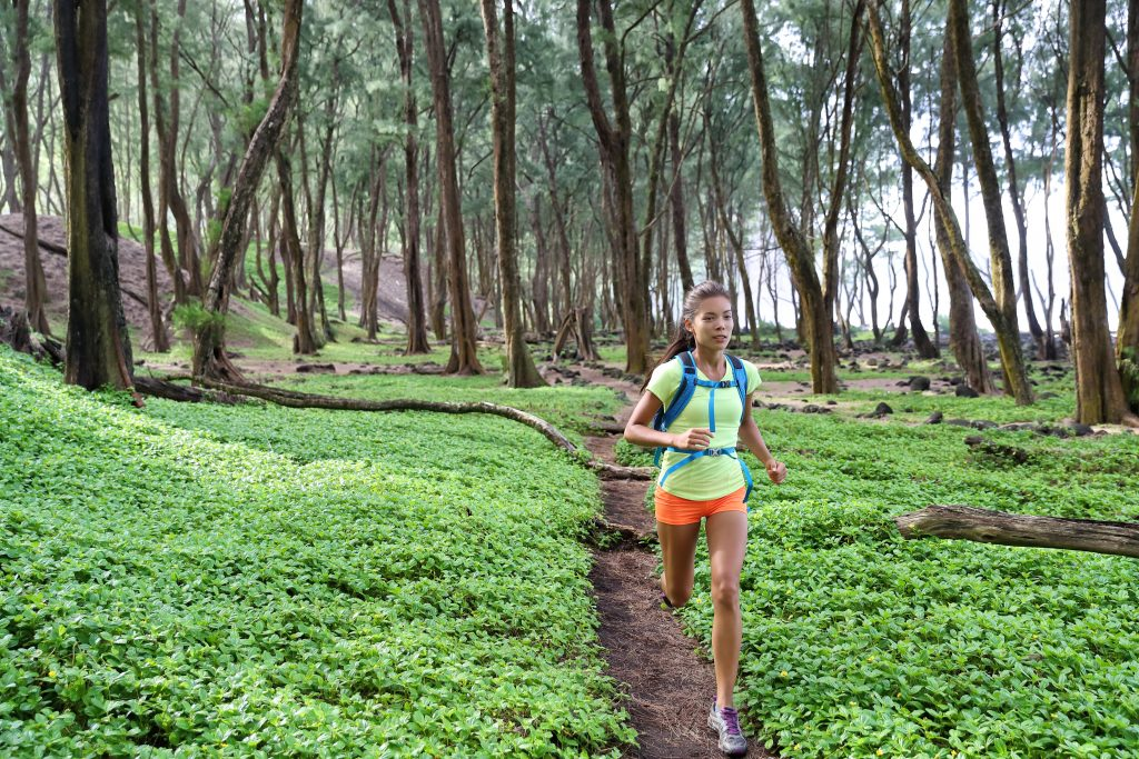 A young female trail runner running through a green forest with an ultra running backpack