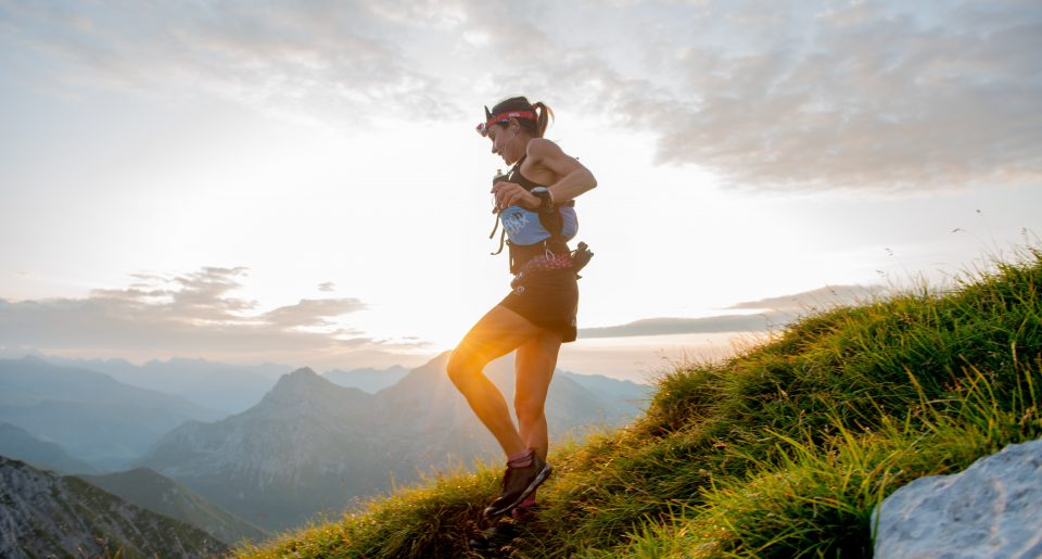 A female ultra runner running through the mountains